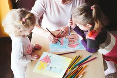Mom with little girls drawing a colorful pictures using pencil c. Mom with little girls drawing a colorful pictures of house and playing children using pencil Stock Images