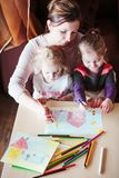 Mom with little girls drawing a colorful pictures using pencil c. Mom with little girls drawing a colorful pictures of house and playing children using pencil Royalty Free Stock Photos