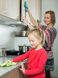 Mom and little kid cleaning at kitchen Royalty Free Stock Photos