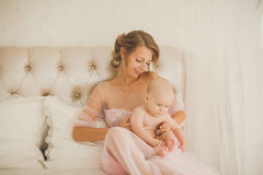 Mom and little kid relaxing at home. Mother and child on a white bed. Mom and little kid relaxing at home. Family having fun together. Bedding and textile for Royalty Free Stock Photos
