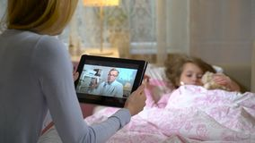 Mom with a little sick daughter gets a doctor`s consultation using video chat at home.