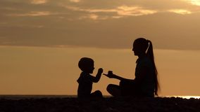 Mom and little son playing on the beach with stones. Sunset time, silhouettes.  stock video