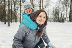 Mom and little son playing in the snow in winter stock photo