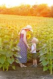 Mom and little son are standing against the blooming field of sunflowers. Vertical frame.  royalty free stock photo
