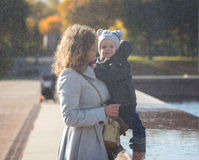Mom and little son under falling water drops. In the park Royalty Free Stock Photos