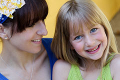 Mom looking at daughter. A young mother lovingly looks at her smiling daughter Royalty Free Stock Images