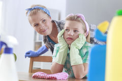 Mom looking at daughter. Mom looking at her sad daughter tired of cleaning Royalty Free Stock Image