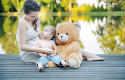 Mom looking at her boy playing teddy bear. Mom looking at her baby playing teddy bear Royalty Free Stock Image