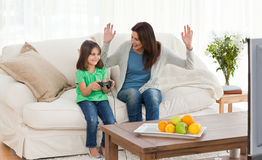 Mom looking at her daughter playing video games. Cheerful mom looking at her daughter playing video games in the living room Royalty Free Stock Image