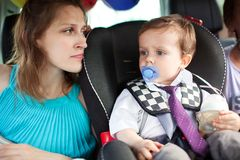 Mom looking at her son in child safety seat Royalty Free Stock Photo