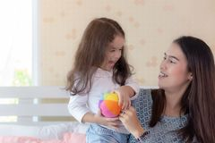 Mom looks at her beautiful little girl or daughter with love. Cute child is laughing and gets relaxed, happiness. They is enjoying royalty free stock photography