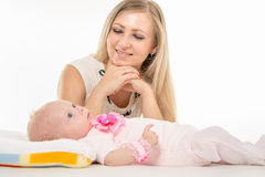 Mom looks at lying on the bed his two-year daughter Stock Photos