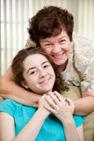 Mom Loves Teen Daughter. Portrait of a mother giving her teen daughter a big hug Stock Photo