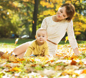Mom lying on the leaves with baby Royalty Free Stock Photos