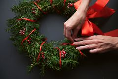 Mom makes a Christmas wreath with her own hands.  stock photos
