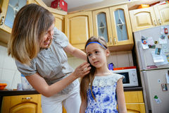 Mom makes daughter hairstyle in the kithen Royalty Free Stock Image