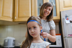 Mom makes daughter hairstyle Stock Photo
