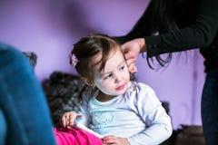 Mom makes hair style for little girl Stock Photos