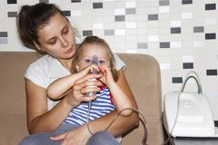 Mom makes inhalation to small daughter at home. Use inhaler for cough and bronchitis. Royalty Free Stock Photos