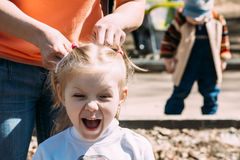 Mom makes little fun girl hairstyle. Little girl grimacing and express their emotions on camera Stock Photo