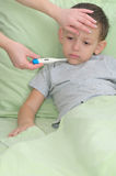 Mom measures the temperature of a patient boy Stock Photo