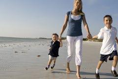 Mom med ungar på en strand fotografering för bildbyråer