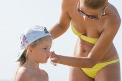 Mom misses on beach little girl's face sunscreen Royalty Free Stock Photos