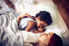 With mom is more beautiful. African American mother and daughter sleeping together. Space for copy. Focus on little girl. Close up stock photos