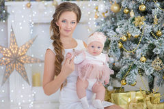 Mom mother with a little sweet and beautiful daughter spends time plays, coos, sitting next to the Christmas tree Stock Photo