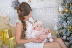 Mom mother with a little sweet and beautiful daughter spends time plays, coos, sitting next to the Christmas tree Royalty Free Stock Photo
