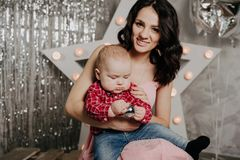 Mom with newborn baby boy son in her arms on the background of Christmas decor stock photography