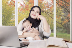 Mom nursing baby while working and daydreaming Stock Photos