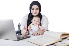 Mom Nursing Baby while Working Stock Photography