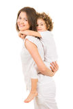 Mom offering piggyback ride to her daughter Royalty Free Stock Images