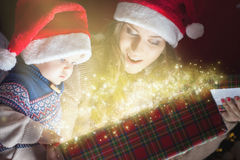 Mom opens the magic box with a gift for child. Christmas holiday! Mother with baby opens the magic box with gift. Box full of magic surprises and secrets! The Stock Image