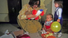 1973: Mom opens up the boy's racecar Christmas gift. stock video