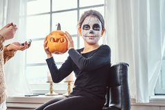 Mom painting daughter face for Halloween party. Mother painting daughter face for Halloween party royalty free stock photos