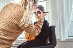 Mom painting daughter face for Halloween party. Mother painting daughter face for Halloween party stock photo