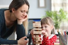 Mom patiently helps her daughter build structure