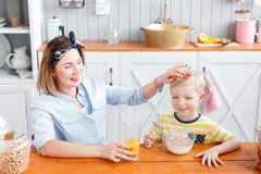 Mom pats the boy on the head. son and young mother in the kitchen eating Breakfast. Son and young mother in the kitchen eating Breakfast. Mom cuts fruit to her Royalty Free Stock Photography