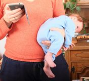 Mom with phone holding newborn baby girl. Young mom in orange pullover playing with smartphone while holding newborn baby girl dressed in blue baby jumpsuit on Royalty Free Stock Photo