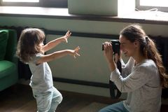 Mom photographer making photo of kid daughter on digital camera Stock Photo