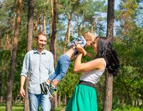 Mom picked up her son and turned him around. Dad stands next to. Her and smiles. Happy family is resting in the park on a sunny day royalty free stock photography