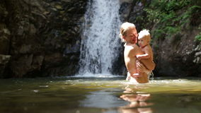 Mom play baby waterfall stock video footage
