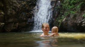 Mom play baby waterfall stock video