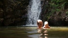 Mom play baby waterfall stock footage