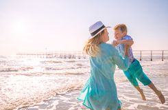 Mom play with her son on the beach. A mom play with her son on the beach stock photo