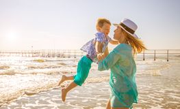 Mom play with her son on the beach. A mom play with her son on the beach royalty free stock images