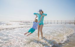 Mom play with her son on the beach. A mom play with her son on the beach royalty free stock photos