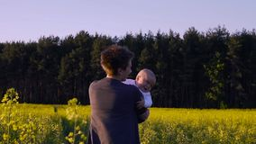 Mom played with the baby in the rapeseed field and dancing.